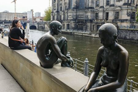 The tourist is resting near Three Girls and a Boy sculpture on Spree River in Berlin, Germany.