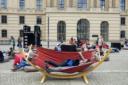 People rest in a hammock on one of Berlins squares, Germany.