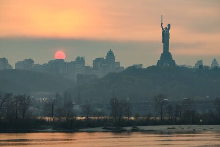 View from left bank at sunset over the Dnieper River, the Motherland Monument and the right-bank part of Kyiv. Ukraine.