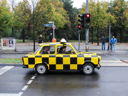 Yellow black taxi Trabant Trabbi, typical car of the former DDR, on street in Berlin. Germany.