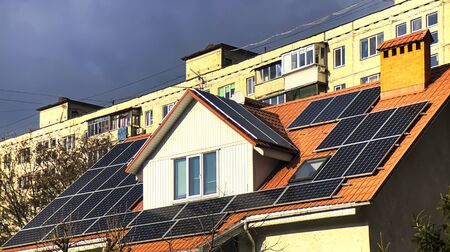 The cottage is equipped with solar panels on the roof with the apartment building behind.