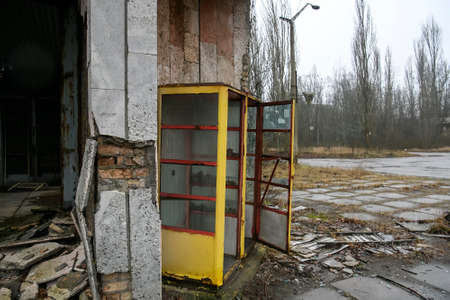Soviet yellow telephone booth on street of abandoned ghost town Pripyat, Chornobyl exclusion zone.  Imagens