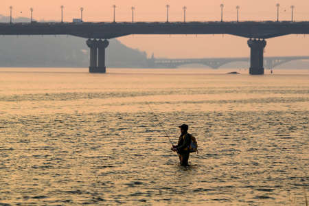 Fisherman stands in the river Dnipro. Sunset over Kyiv and the Motherland Monument.  Reklamní fotografie