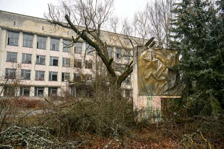 Abandoned ghost town Prypiat. Overgrown trees and collapsing buildings in Chornobyl exclusion zone.
