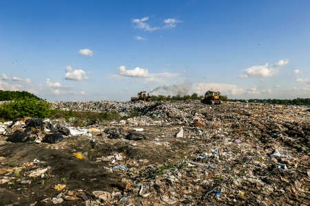Seagulls fly over piles of garbage. A bulldozer tractor works at a large landfill near Kyiv, Ukraine. May 2016