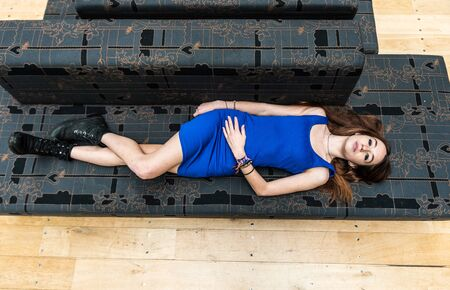 Portrait of an attractive 18 year old white woman lying on a gray couch, wearing a royal blue night dress