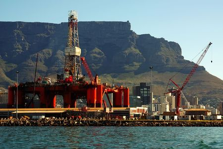 boring frame: oil- rig been repared in the bay into a big city  with tower buildings near ocean and mountains. cape town, south africa