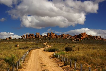 unsurfaced road: Country unsurfaced road to rhe yellow red cliffs. Yellow sand and green bushes, deep blue cloudy sky. Mountains of South Africa Stock Photo