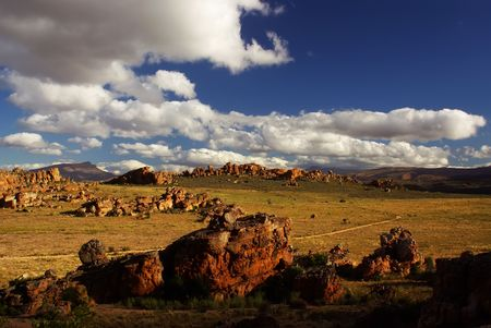 unsurfaced road: Yellow red cliffs and stones. Country unsurfaced road, Yellow ground and green bushes, deep blue cloudy sky. Mountains of South Africa