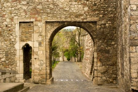 macadam: view through old stone arc on pavement in royal palace in budapest hungary