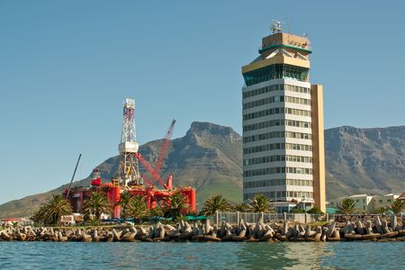 oil- rig in the bay into a big city  with tower buildings near ocean and mountains. cape town, south africa
