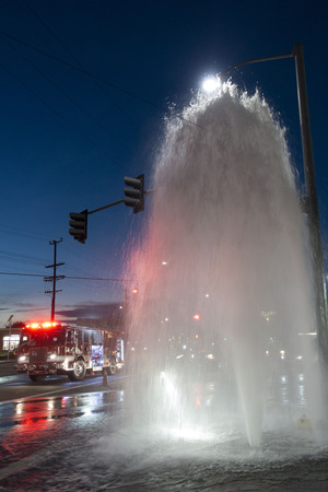accident fire truck: A fire truck arrives at an intersection filled with water from a broken fire hydrant shooting water twenty-five feet into the air beneath a street lamp at sunset.