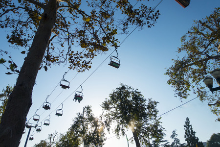 chair on the lift: Chair lift above trees at sunset. Stock Photo