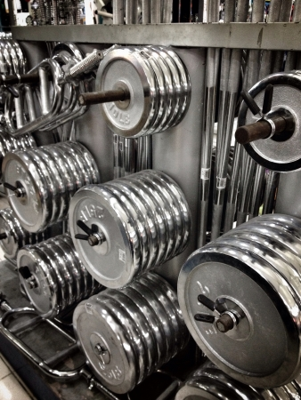 muscle toning: A bunch of weights gym equipments used for weight lifting muscle toning or conditioning. Circular shapes.
