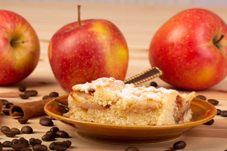Apple pie on a plate with apples, coffee and cinnamon in the background