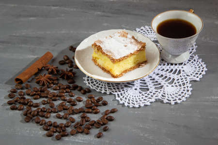 Cake with a cup of coffee with coffee beans and cinnamon and anise