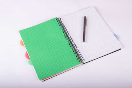 Opened green notebook with a pen on a white background 写真素材