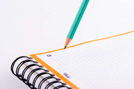 Green pencil writing in a checkered notebook. A card with an orange frame.