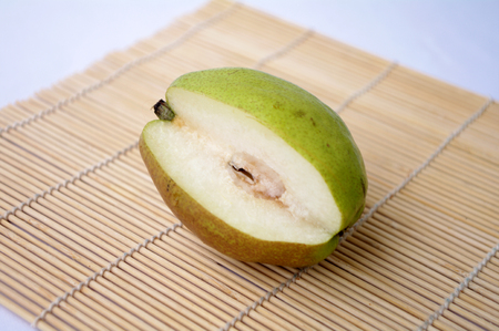 fruitage: Close up view of a pear on a bamboo mat