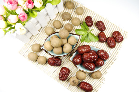 Dry longan and jujube in bowls on bamboo mat