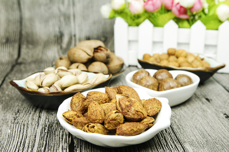 Variety of nuts in separate plates on wooden background