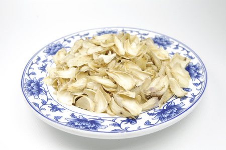 Dried lily in a plate on white background