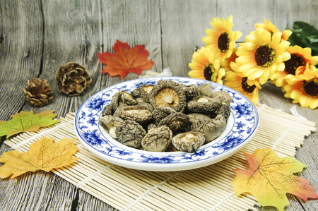 Dried mushrooms on a bamboo mat on wooden background Stock Photo