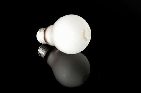 Frosted light bulb on reflective black surface. Conceptual image of thought process with successful inspirational result. Bright idea from reflective effort.