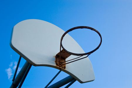 Old basketball hoop, no net, against a bright blue sky. Stock Photo
