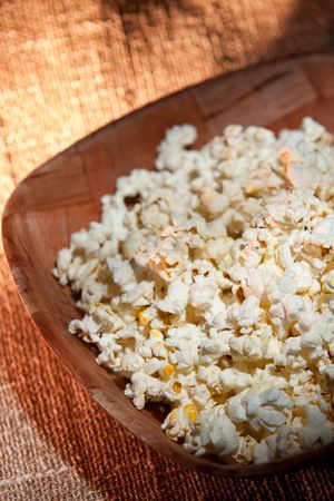 Bowl of tasty  popcorn on a rustic texturized background