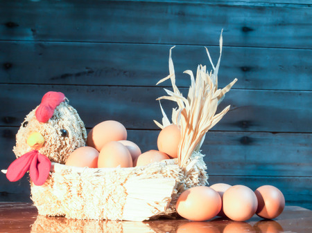 Still light eggs in straw hens on wood and old wood background  photo