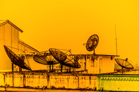 rf: A few satellite dishes on a roof in the sunset
