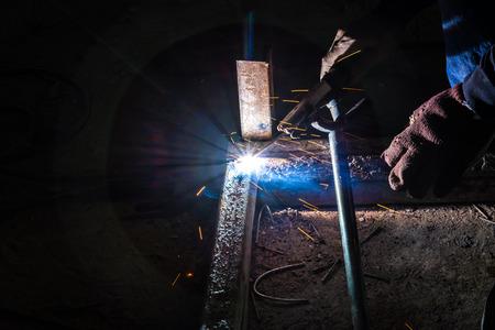 Worker are welding steel on low light. photo