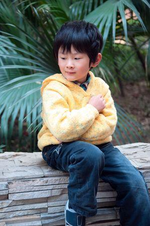 Reflection of the boy sitting in windowsill