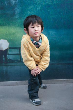 Street-side billboards in front of a little boy