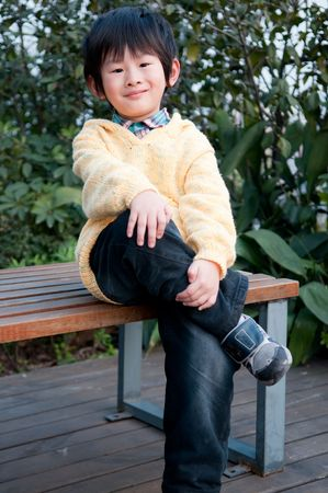 Boy sitting on a park bench, exposing proud expression