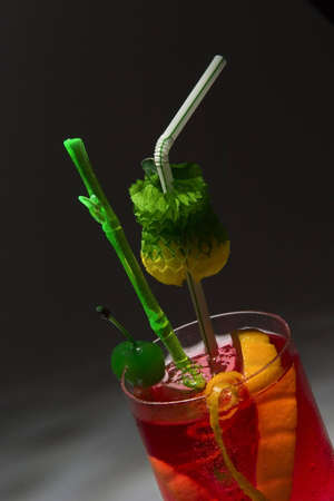 Red drink with green cherry. Studio shot. photo