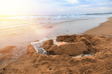 Waves wash away sand castles on beach the sea