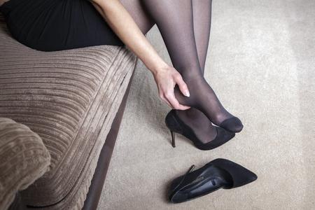 Tired businesswoman feet pain Foto de archivo