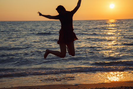 Girl jumping against sunrise. Happy Woman relax on the beach during holiday