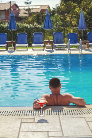 Young Man enjoys in swimming pool with cocktail alcohol drink, Holliday relax and sunbathe