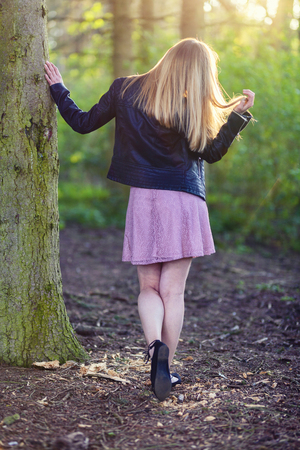 Woman in dress touches a tree in a forest