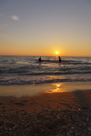 Happy friends at sunset sea beach. Family enjoy a holiday on the beach