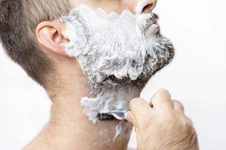 Man is shaving his beard with a razor