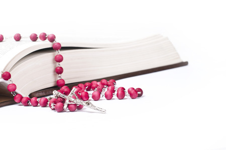 red rosary on a book  white background  studio shot photo