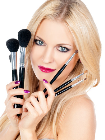 Beautiful woman with makeup brushes photo
