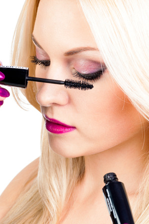 cilia: Long eyelashes. Woman putting mascara makeup
