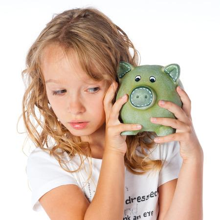 Pretty little girl and piggy bank Reklamní fotografie