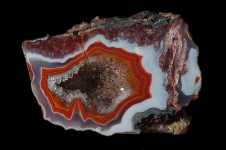 Agate. A cross section of the stone with geode on a black background