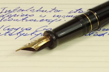 Fountain pen with gold, ornate nib on a notebook. Archivio Fotografico